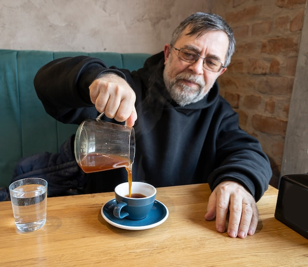 Retrato de homem sênior desfrutando de uma xícara de café alternativo no café