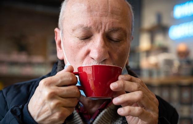 Retrato de homem sênior desfrutando de uma xícara de café no café