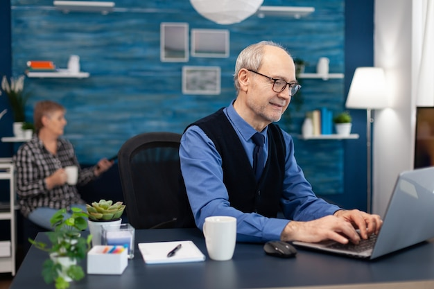 Retrato de homem sênior digitando no teclado do laptop, trabalhando no projeto
