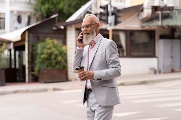 Retrato de homem sênior elegante falando ao telefone