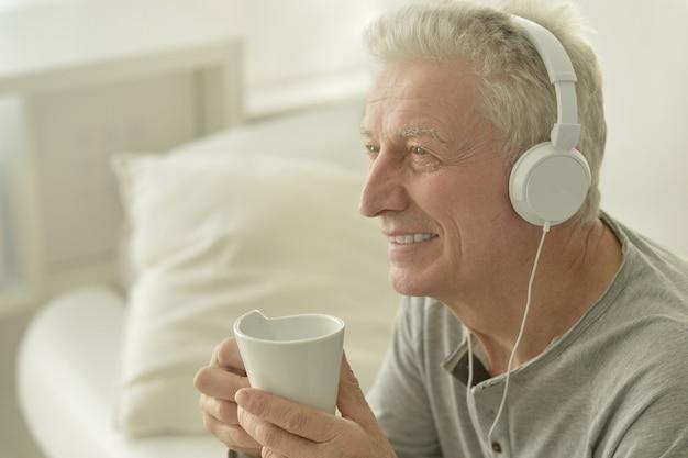 Retrato de homem sênior em fones de ouvido e café