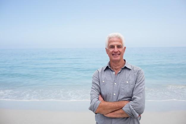 Retrato de homem sênior em pé com os braços cruzados na praia