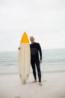 Retrato de homem sênior em roupa de mergulho segurando uma prancha de surf