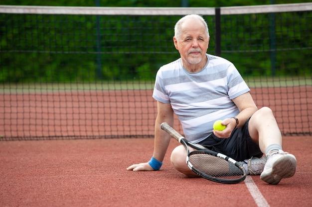 Retrato de homem sênior jogando tênis em um esporte aposentado, conceito de esporte