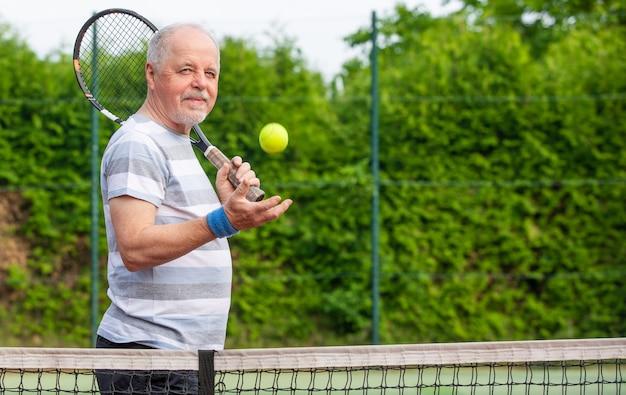 Retrato de homem sênior jogando tênis em um lado de fora, esportes aposentado, conceito de esporte