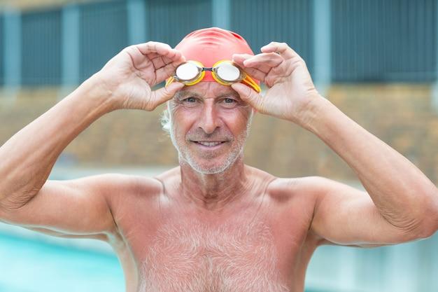 Retrato de homem sênior segurando óculos de natação ao lado da piscina