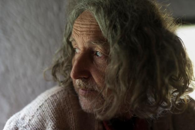 Retrato de homem sênior sério de cabelos compridos cinza, olhando para longe.