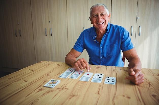 Retrato de homem senior sorridente, apontando para um cartão