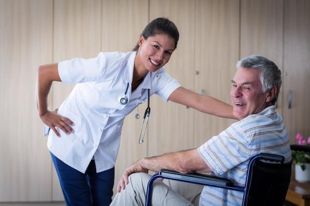 Retrato de homem senior sorridente e médica na sala de estar