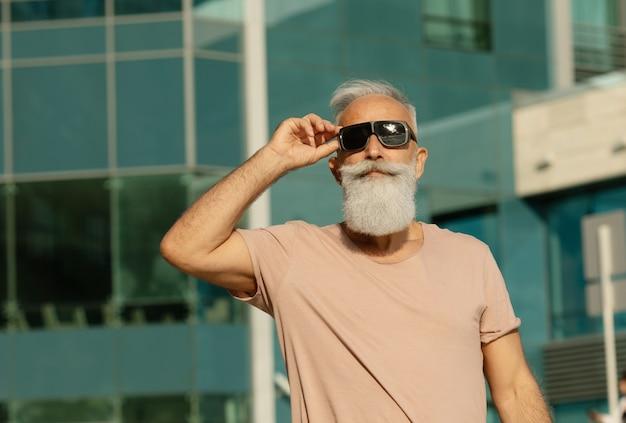 Retrato de homem sênior, vestindo roupas casuais, olhando para longe. homem maduro com barba andando pela rua num dia de verão.