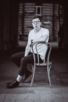Retrato de homem sentado na cadeira com camiseta branca e óculos escuros na rua
