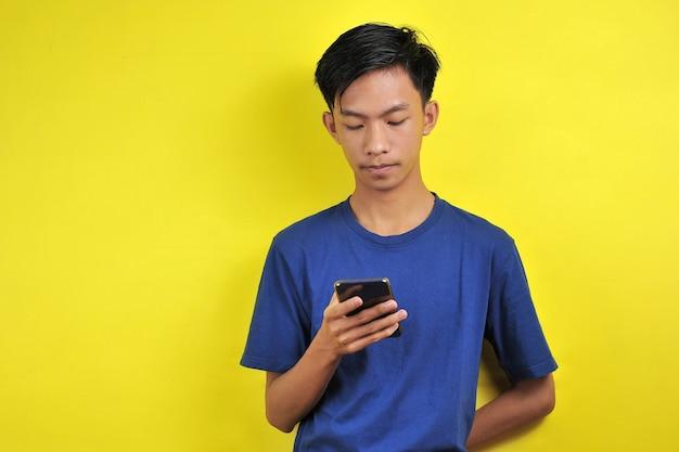 Retrato de homem sério asiático usando smartphone isolado em fundo amarelo
