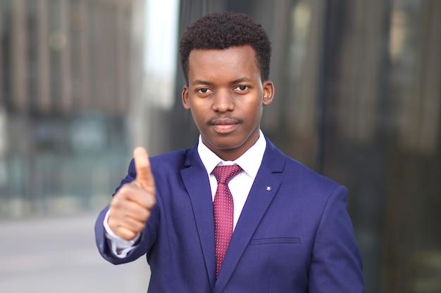 Retrato de homem sério bonito, negro afro-americano jovem empresário, trabalhador de escritório em terno formal com gravata aparecendo o polegar, como gesto. conceito de negócios.