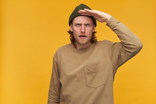 Retrato de homem sério com barba e cabelo loiro. usando gorro verde e suéter bege. segura a palma da mão ao lado da testa e olha para longe. isolado sobre a parede amarela