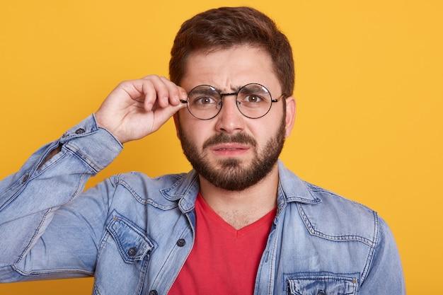 Retrato de homem sério, com cabelos escuros e barba tocando seus óculos, masculino vestindo jaqueta jeans elegante, posando contra parede amarela