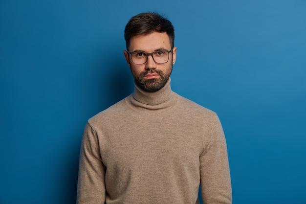 Retrato de homem sério e bonito tem cabelo escuro, cerdas grossas, olha diretamente para a câmera, usa óculos ópticos e blusa de gola alta, isolado sobre fundo azul