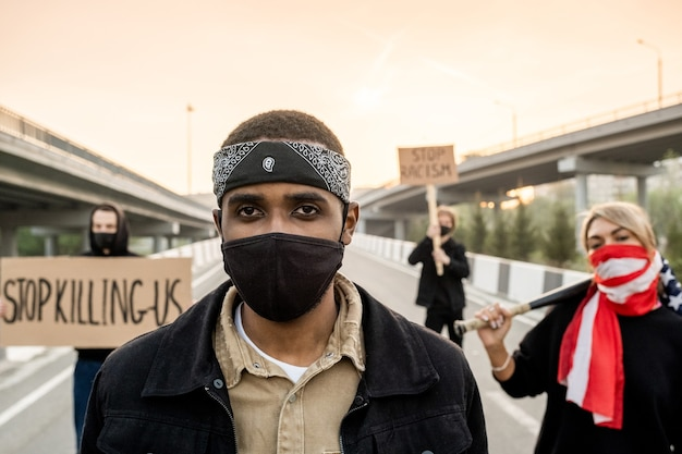 Retrato de homem sério e brutal com máscara usando bandana e máscara facial, em pé na rua contra pessoas protestando com placas
