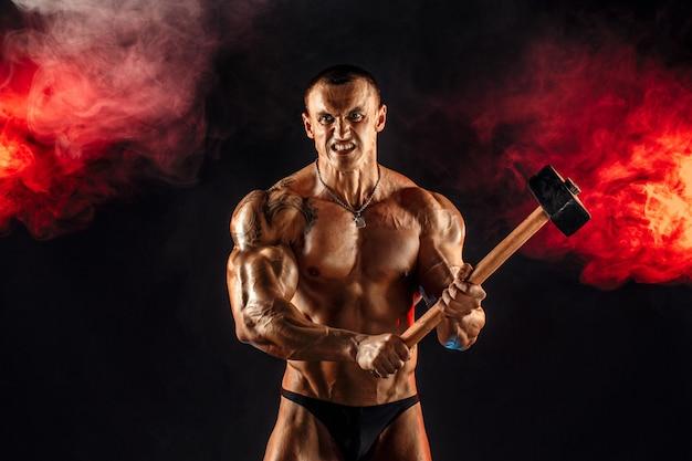 Retrato de homem sério e musculoso em topless com uma marreta