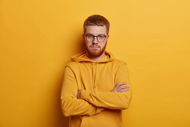 Retrato de homem sério fica em um gesto confiante, mantém os braços cruzados, tem óculos óticos e barba ruiva, usa capuz, posa contra a parede amarela. tem expressão assertiva.