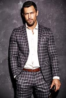 Retrato de homem sexy modelo masculino bonito vestido elegante terno posando perto da parede cinza