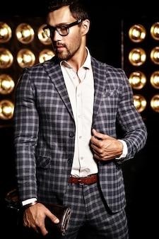 Retrato de homem sexy modelo masculino moda sexy vestido elegante terno em fundo preto luzes de estúdio em copos