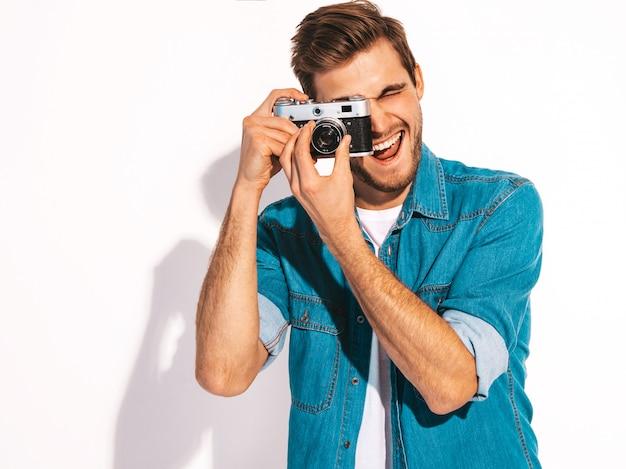 Retrato de homem sorridente bonito vestindo roupas jeans de verão. modelo masculino tirando foto na câmera fotográfica vintage velha.