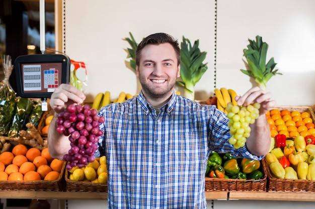 Retrato de homem sorridente em camisa vendendo uvas maduras na loja. caixas com frutas e vegetais