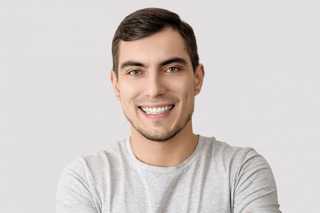 Retrato, de, homem sorridente, em, cinzento, t-shirt, ligado, luz, fundo, para, anunciando
