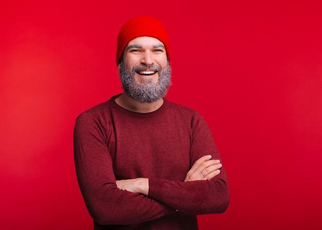 Retrato de homem sorridente feliz em roupas de inverno, perto de espaço vermelho