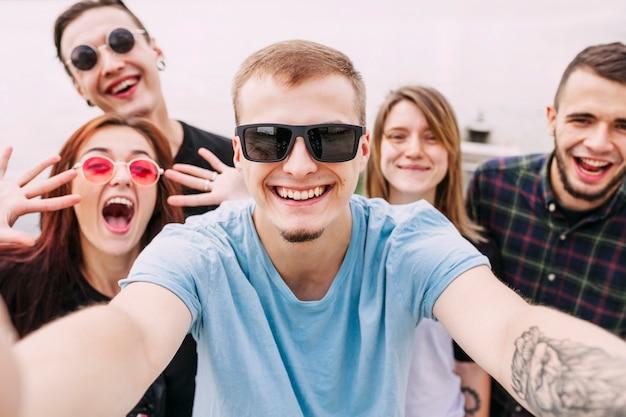 Retrato, de, homem sorridente, levando, selfie, com, amigos