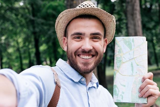 Retrato, de, homem sorridente, segurando, mapa, levando, selfie, em, ao ar livre