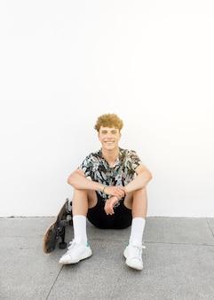 Retrato, de, homem sorridente, sentando, com, skateboard, contra, parede branca