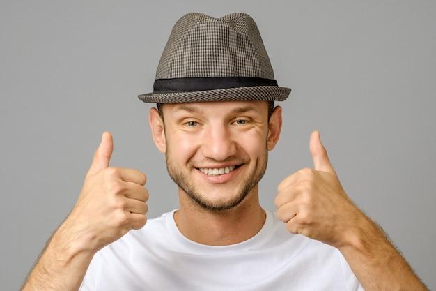 Retrato de homem sorrindo e mostrando dois polegares para cima