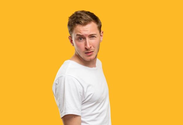 Retrato de homem suspeito. olhar de advertência. cara cético, levantando uma sobrancelha isolada em fundo laranja.