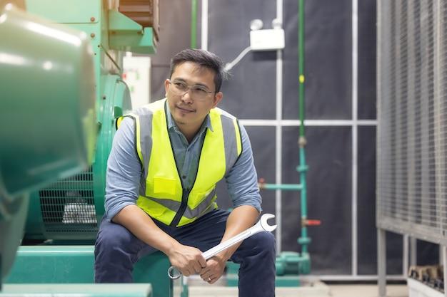 Retrato de homem trabalhador ou técnico segurar a chave inglesa, sorrir e ficar na sala do gerador