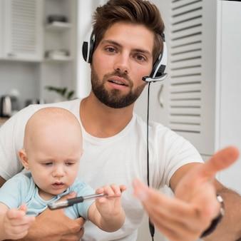 Retrato de homem trabalhando segurando um bebê