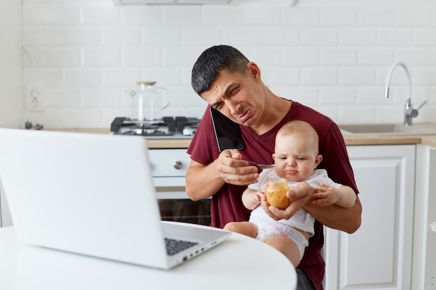 Retrato de homem triste e chateado, vestindo camiseta marrom casual, sentado com a filha ou filho de joelhos, falando ao telefone e chorando, precisa trabalhar e cuidar do bebê, não tem tempo.