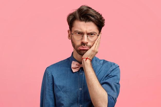 Retrato de homem triste e estressante mantém a mão na bochecha, parece desesperado, sente dor de dente, tem alguns problemas