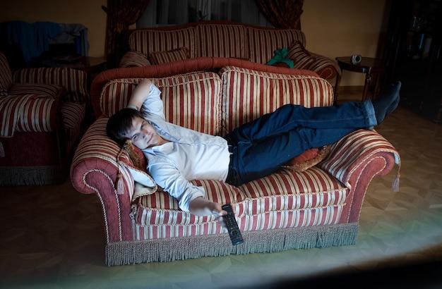 Retrato de homem trocando de canal de tv no sofá à noite
