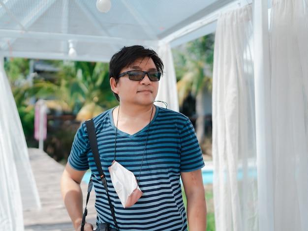 Retrato de homem turista asiático em roupas casuais pendurando máscara protetora de tecido no pescoço durante fotografia tirada em cortina branca decorada ao ar livre no jardim