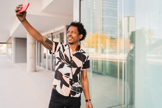 Retrato de homem turista carregando mala e tirando selfie com telefone ao ar livre na rua