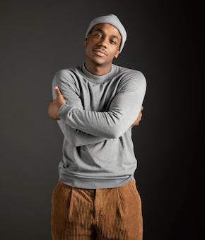 Retrato de homem usando boné com os braços cruzados