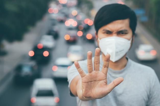 Retrato de homem usando máscara higiênica facial nariz ao ar livre. ecologia, carro de poluição do ar, conceito de proteção ambiental e de vírus saúde da gripe contra poeira tóxica cobriu a cidade de um efeito de saúde.
