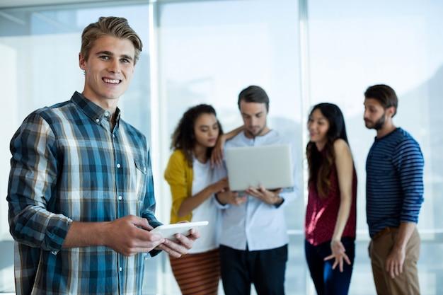 Retrato de homem usando tablet digital no escritório enquanto colega discutindo atrás
