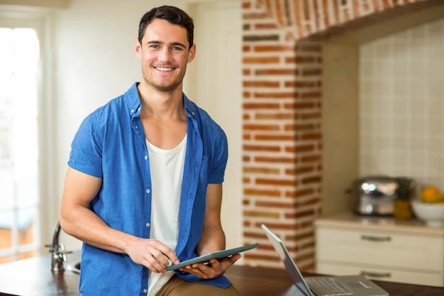 Retrato, de, homem, usando, tablete digital, com, laptop, em, cozinha