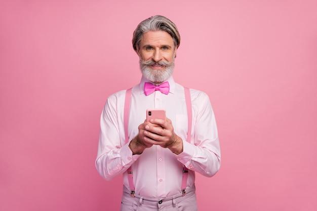 Retrato de homem usando telefone digital, posando na parede rosa