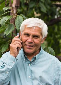 Retrato de homem velho bonito usando smartphone ao ar livre