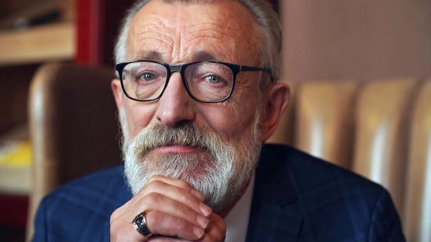 Retrato de homem velho de óculos e terno clássico, sentado na cadeira