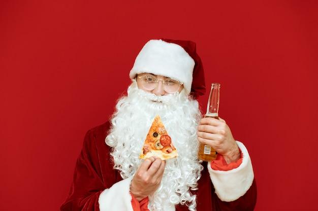 Retrato de homem vestido de papai noel segurando uma garrafa de cerveja e uma fatia de pizza