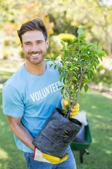 Retrato de homem voluntário segurando a planta